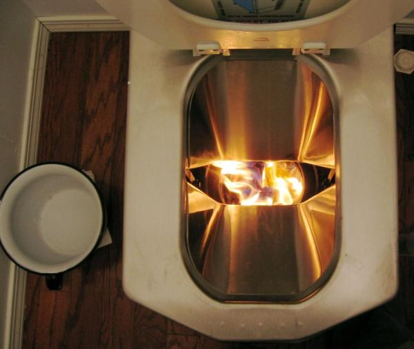 incinerating toilet in action with flames exposed